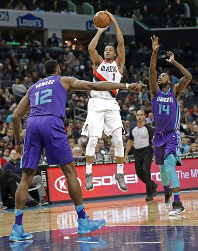 Portland Trail Blazers' CJ McCollum (3) shoots between Charlotte Hornets' Dwight Howard (12) and Michael Kidd-Gilchrist (14) during the first half of an NBA basketball game in Charlotte, N.C., Saturday, Dec. 16, 2017. (AP Photo/Chuck Burton)