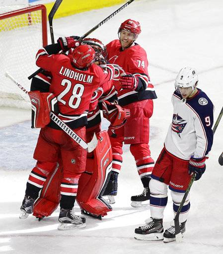 Carolina Hurricanes' Elias Lindholm (28), of Sweden, and Jaccob Slavin (74) congratulate goalie Scott Darling following their win over the Columbus Blue Jackets in an NHL hockey game in Raleigh, N.C., Saturday, Dec. 16, 2017. Blue Jackets' Artemi Panarin (9), of Russia, skates away. (AP Photo/Gerry Broome)