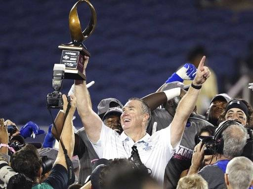 Georgia State head coach Sean Elliott hoists the championship trophy after winning the Cure Bowl NCAA college football game against Western Kentucky, Saturday, Dec. 16, 2017 in Orlando, Fla. Georgia State won 27-17. (Stephen M. Dowell/Orlando Sentinel via AP)