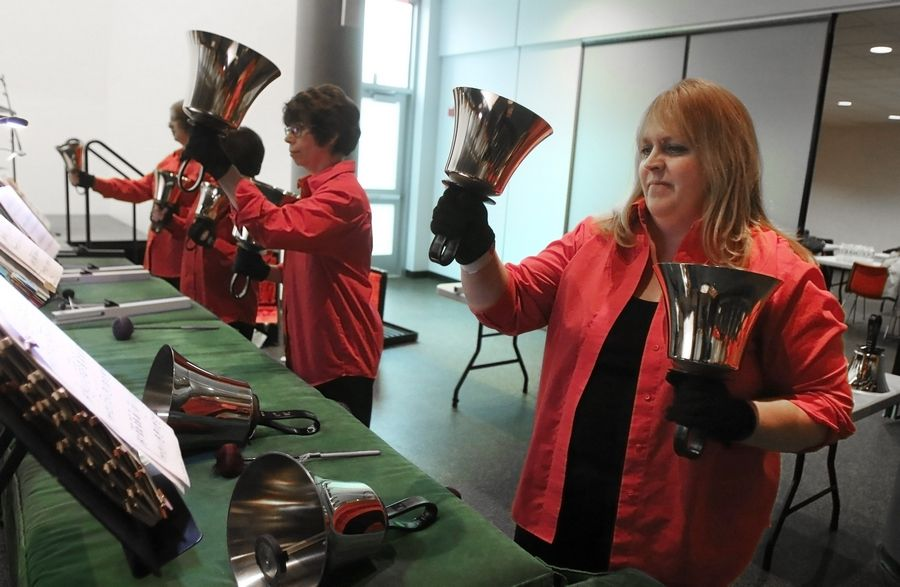 Annemarie Barry, right, and Teri DeClerck play bass bells during the Random Ringers holiday concert Sunday at the Poplar Creek Public Library in Streamwood. More than 100 people listened to the bell ringers perform holiday songs.