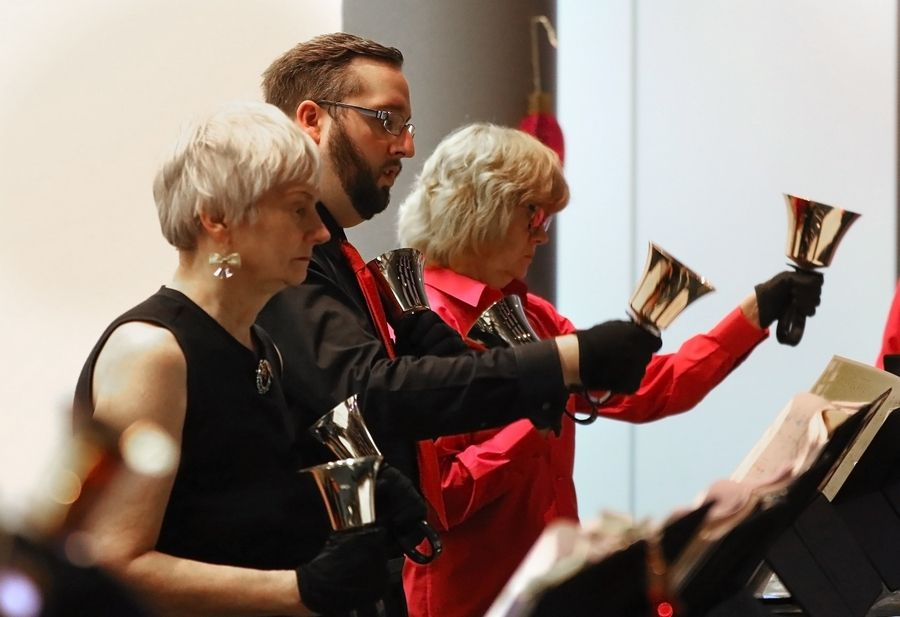 Joanne Miller, left, Ben Hafner and Jean Streeter play the bells during the Random Ringers holiday concert Sunday at the Poplar Creek Public Library in Streamwood.