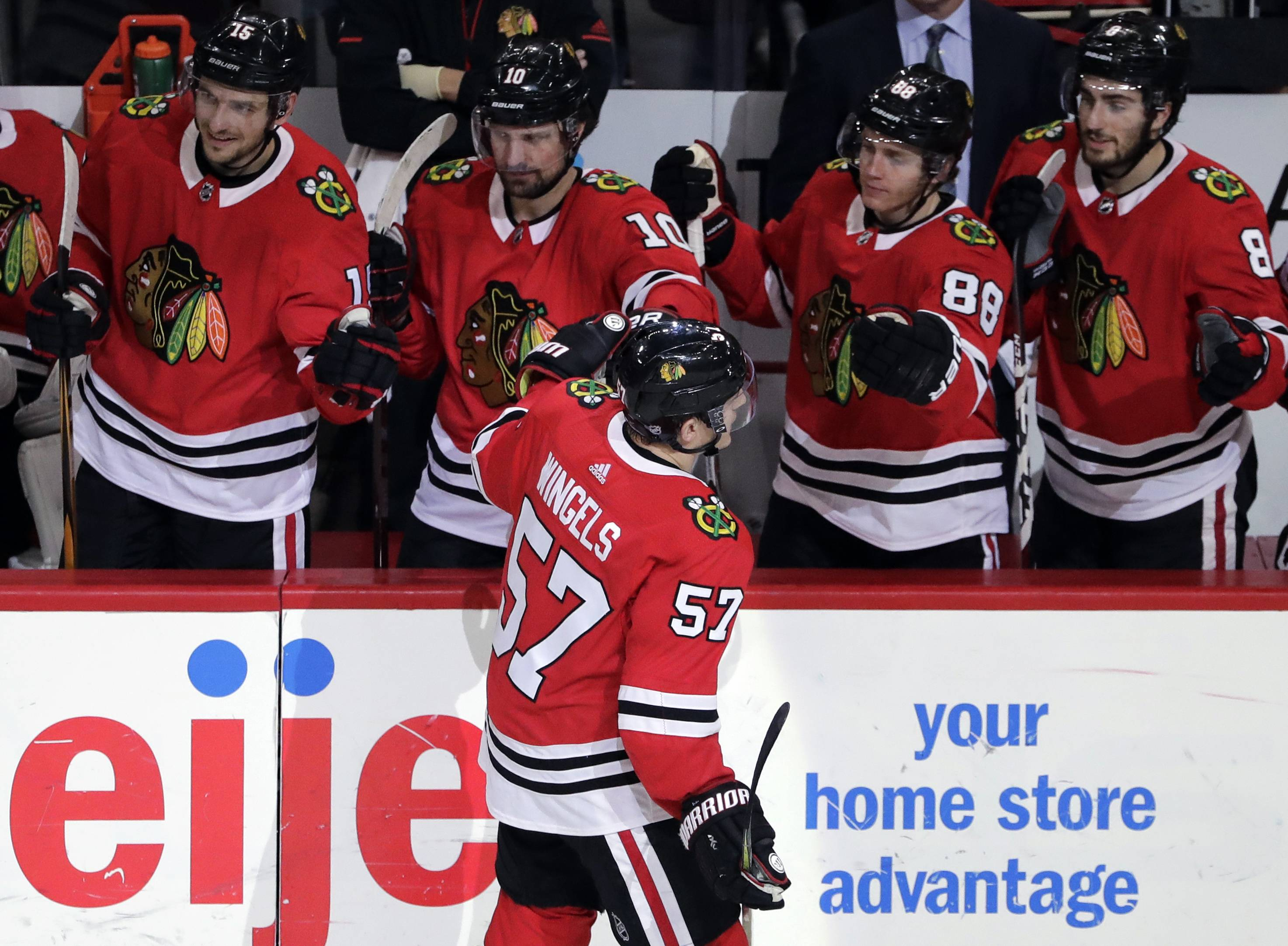 Chicago Blackhawks right wing Tommy Wingels (57) celebrates with teammates after scoring a goal against the Minnesota Wild during the third period of an NHL hockey game, Sunday, Dec. 17, 2017, in Chicago. The Blackhawks won 4-1. (AP Photo/Nam Y. Huh)