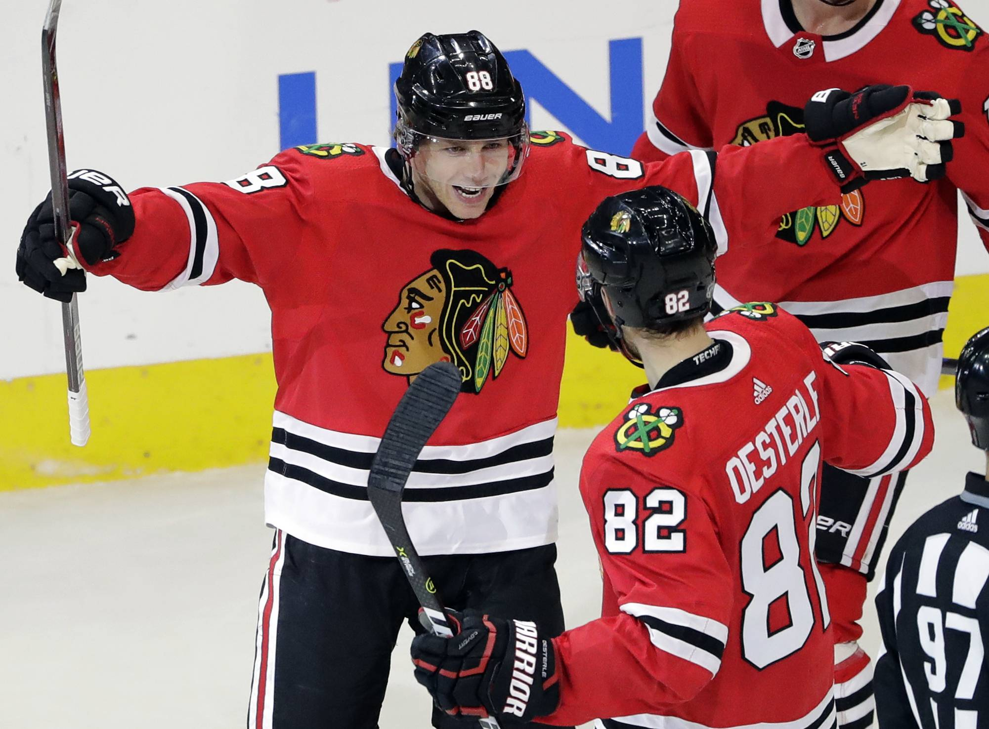 Chicago Blackhawks right wing Patrick Kane, celebrates with defenseman Jordan Oesterle after scoring a goal against the Minnesota Wild during the second period of an NHL hockey game, Sunday, Dec. 17, 2017, in Chicago. (AP Photo/Nam Y. Huh)