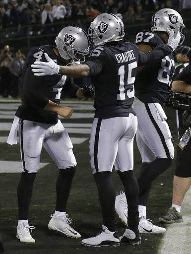 Oakland Raiders quarterback Derek Carr (4) and wide receiver Michael Crabtree (15) celebrate after connecting on a touchdown during the second half of an NFL football game against the Dallas Cowboys in Oakland, Calif., Sunday, Dec. 17, 2017.