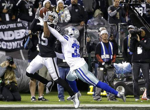 Oakland Raiders wide receiver Michael Crabtree (15) catches a touchdown pass in front of Dallas Cowboys cornerback Chidobe Awuzie (33) during the second half of an NFL football game in Oakland, Calif., Sunday, Dec. 17, 2017.