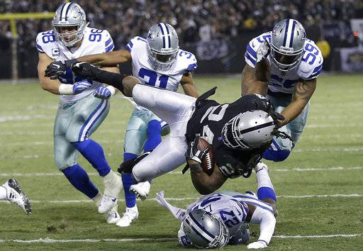 Oakland Raiders running back Marshawn Lynch (24) is tackled by Dallas Cowboys defenders during the second half of an NFL football game in Oakland, Calif., Sunday, Dec. 17, 2017.