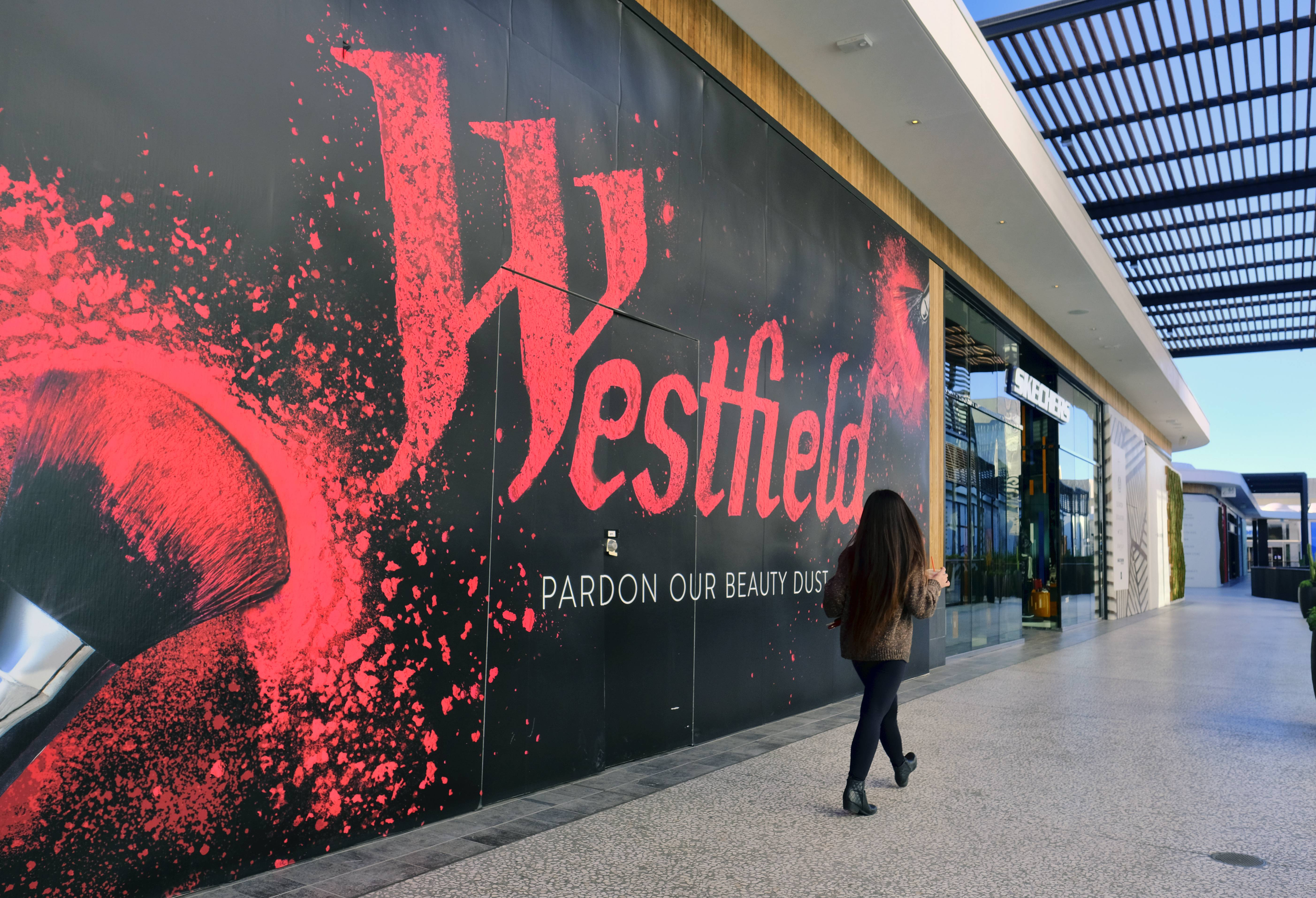 A person walks by a new shop being installed at the Westfield Century City Mall in the Century City section of Los Angeles. Shoppers who brave the crowds at the mall this holiday season may notice changes beyond the seasonal decor and signs advertising big discounts. Many malls have spent billions to transform themselves into destinations where shopping is almost secondary, adding swanky dining options, premium movie theaters and other entertainment options.
