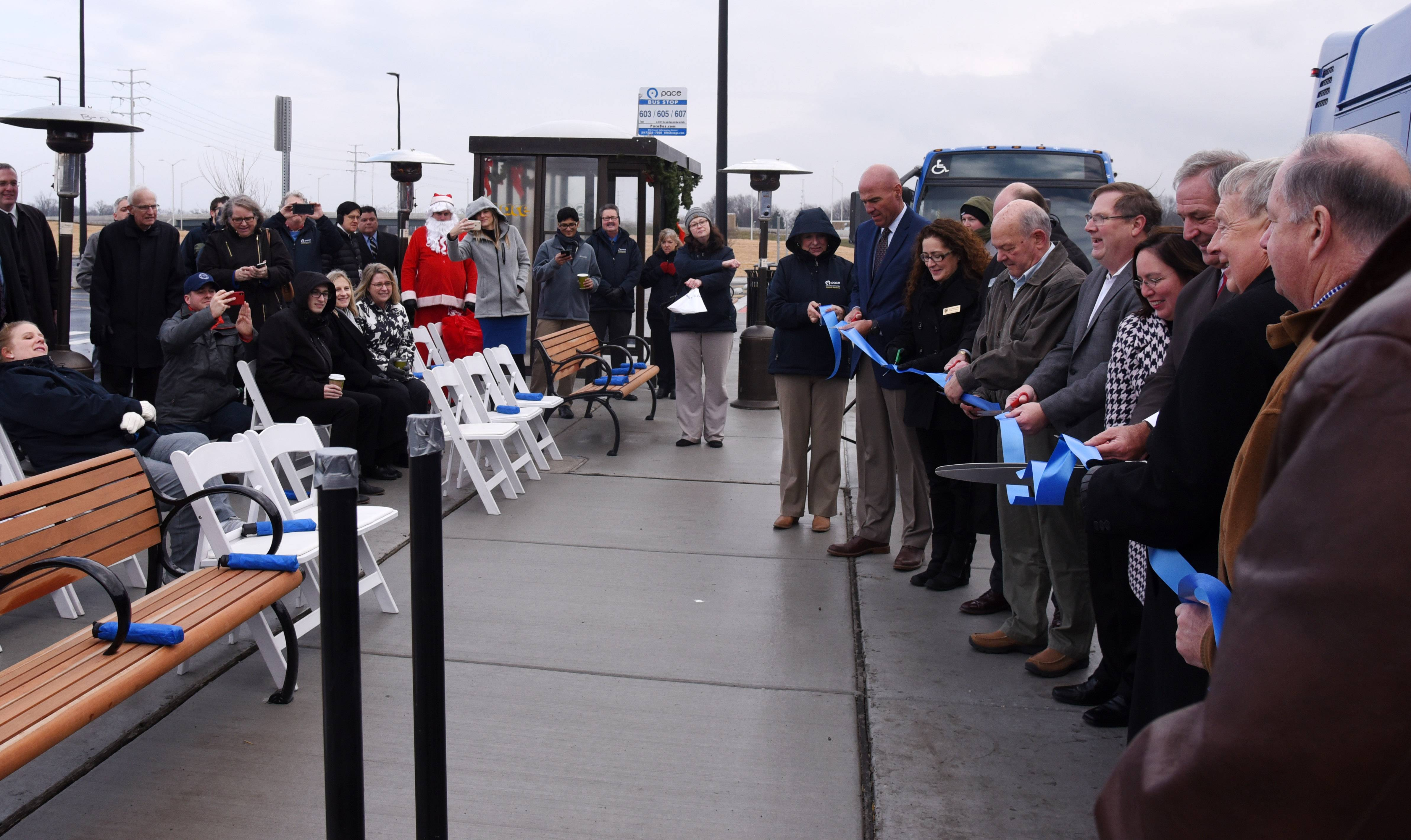 A ceremonial ribbon is cut as Pace opens a new park-n-ride lot at I-90 and Route 25 in Elgin Monday.