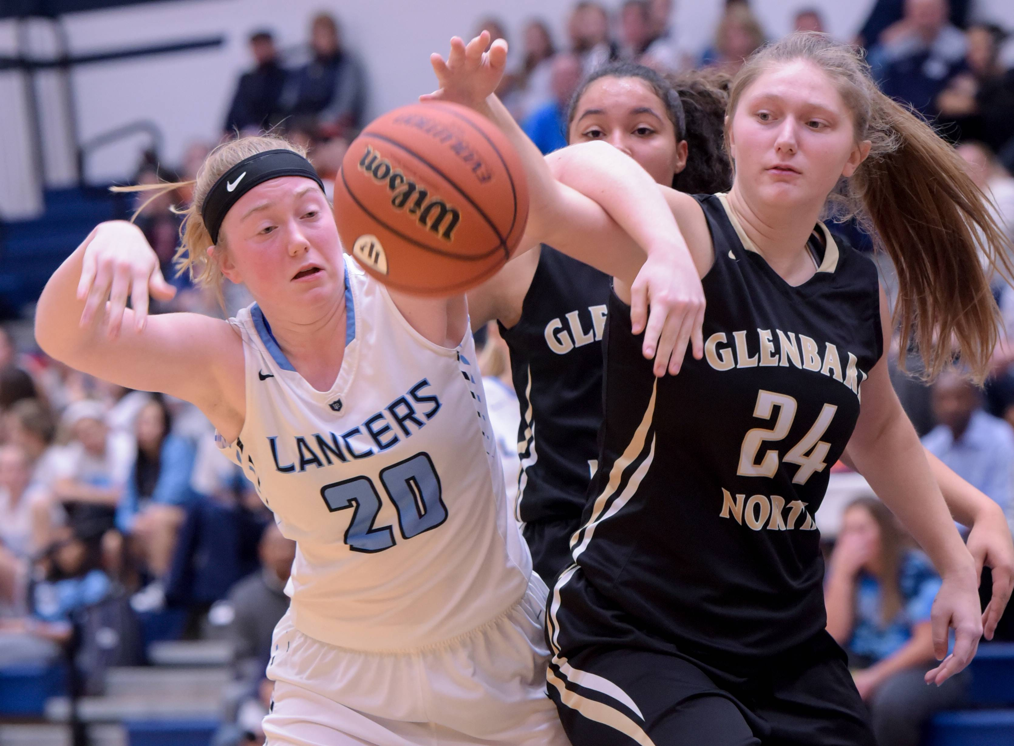Lake Park's Daina Riser (20) and Glenbard North's Karissa Chalus (24) get tangled up as they go after the ball during varsity girls basketball game in Roselle on December 18, 2017.