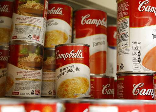 In this Monday, May 22, 2017, photo, cans of Campbell's soup are displayed at a supermarket in Englewood, N.J. Campbell Soup announced Monday, Dec. 18, 2017, that it will spend $4.87 billion in cash for Snyder's-Lance, gorging on a snack market that has grown increasingly competitive. (AP Photo/Seth Wenig)