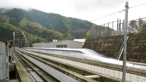 FILE - In this April 21, 2015, file photo, a Japanese maglev train that is the fastest passenger train in the world runs on the Maglev Test Line in Tsuru, west of Tokyo. Prosecutors raided the headquarters of several of Japan's biggest construction companies in an investigation into alleged collusion on bids for a multibillion dollar high-speed maglev train line. News reports Tuesday, Dec. 19, 2017 showed investigators heading into the headquarters of Taisei Corp. and Obayashi Corp., two of four companies targeted in the probe. (Katsuya Miyagawa/Kyodo News via AP, File)
