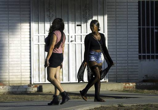 In this Wednesday, Nov. 15, 2017 photo, an undercover sheriff's deputy posing as a prostitute, left, talks with a woman passing by who identified herself as a prostitute in Compton, Calif., a city some 15 miles south of Los Angeles. For hours, Los Angeles County sheriff's deputies listen to the same scenario play out over and over: men pull up alongside a woman pacing in front of an abandoned storefront in Compton and proposition her to have sex with him. They soon found themselves in handcuffs. The women were undercover Los Angeles County sheriff's deputies posing as prostitutes in a sting operation aimed at stemming the demand in the commercial sex industry. (AP Photo/Reed Saxon)