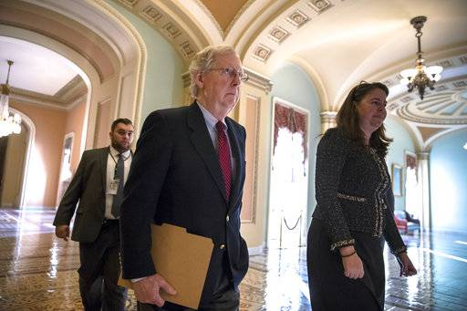 Senate Majority Leader Mitch McConnell, R-Ky., accompanied at right by Secretary for the Majority Laura Dove, walks to the chamber as Republicans in the House and Senate plan to pass the sweeping $1.5 trillion GOP tax bill on party-line votes, at the Capitol in Washington, Monday, Dec. 18, 2017. (AP Photo/J. Scott Applewhite)