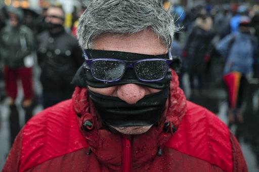 A man takes part in a flash mob in Bucharest, Romania, Sunday, Dec. 17, 2017. Protesters braved low temperatures and rain covering their mouths and eyes with black ribbons during a flash mob outside the government headquarters against planned modifications to Romanian justice legislation that critics say would render it less effective in punishing high-level corruption. (AP Photo/Vadim Ghirda)