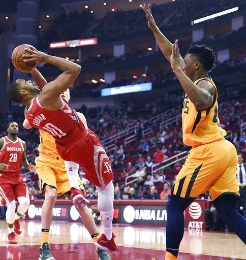Houston Rockets guard Eric Gordon, left, falls down shooting as Utah Jazz guard Donovan Mitchell, right, defends during the first half of an NBA basketball game, Monday, Dec. 18, 2017, in Houston. (AP Photo/Eric Christian Smith)