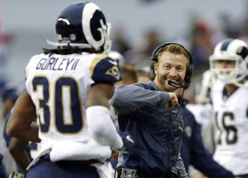 Los Angeles Rams head coach Sean McVay, right, greets running back Todd Gurley (30) after Gurley scored a touchdown in the second half of an NFL football game, against the Seattle Seahawks, Sunday, Dec. 17, 2017, in Seattle. The score was Gurley's fourth touchdown of the game. (AP Photo/John Froschauer)