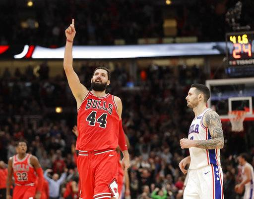 Chicago Bulls' Nikola Mirotic celebrates his team's pulling away from the Philadelphia 76ers as 76ers' JJ Redick looks on during the second half of an NBA basketball game Monday, Dec. 18, 2017, in Chicago. (AP Photo/Charles Rex Arbogast)