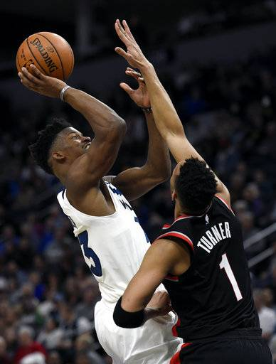 Minnesota Timberwolves guard Jimmy Butler, left, shoots against Portland Trail Blazers guard Evan Turner (1) during the fourth quarter of an NBA basketball game on Monday, Dec. 18, 2017, in Minneapolis. The Timberwolves won 108-107. (AP Photo/Hannah Foslien)