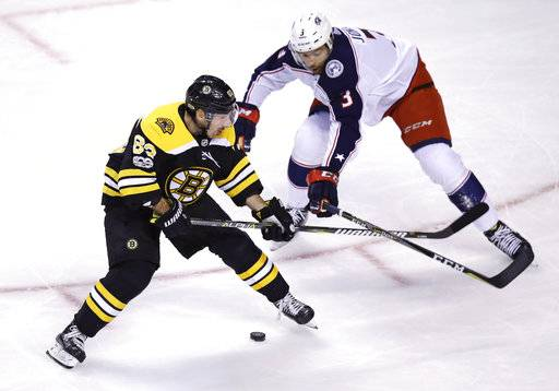 Boston Bruins left wing Brad Marchand (63) controls the puck and pivots around Columbus Blue Jackets defenseman Seth Jones (3) during the first period of an NHL hockey game in Boston, Monday, Dec. 18, 2017. (AP Photo/Charles Krupa)