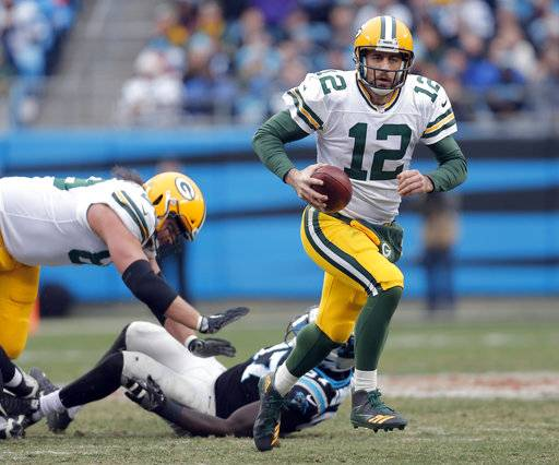 Green Bay Packers' Aaron Rodgers (12) scrambles against the Carolina Panthers during the second half of an NFL football game in Charlotte, N.C., Sunday, Dec. 17, 2017. (AP Photo/Bob Leverone)
