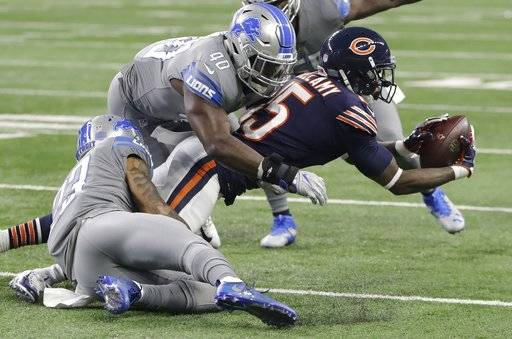 Chicago Bears wide receiver Josh Bellamy (15) is tackled by Detroit Lions cornerback Darius Slay (23) and linebacker Jarrad Davis (40) during the first half of an NFL football game, Saturday, Dec. 16, 2017, in Detroit. (AP Photo/Carlos Osorio)