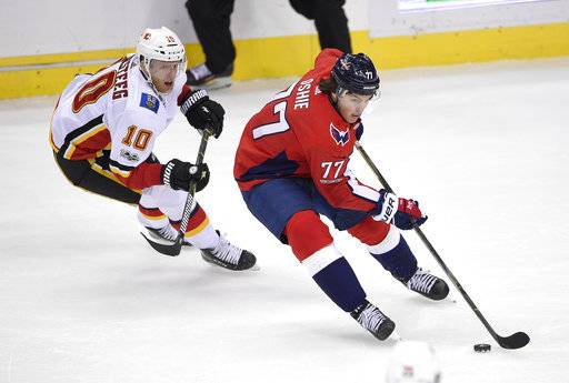 In this Nov. 20, 2017 photo, Washington Capitals right wing T.J. Oshie (77) skates with the puck past Calgary Flames right wing Kris Versteeg (10) during the third period of an NHL hockey game in Washington. Oshie is expected to return to the Washington Capitals' lineup Tuesday at the Dallas Stars after missing six games with a concussion. (AP Photo/Nick Wass)