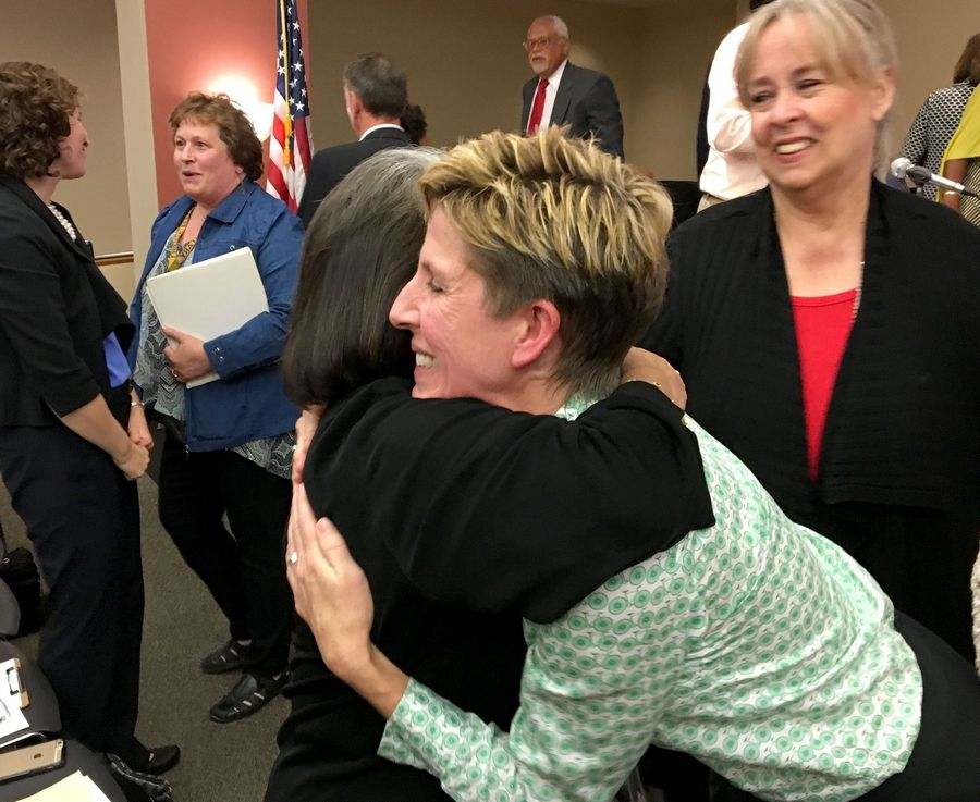 Kerry Kelly, president of the Elgin Charter School Initiative, gets congratulatory hugs after the group won state approval for a new charter school in Elgin.