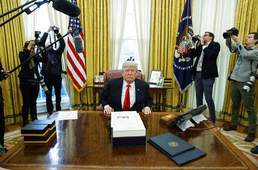 President Donald Trump speaks to reporters Friday after signing the tax bill and continuing resolution to fund the government in the Oval Office of the White House in Washington.