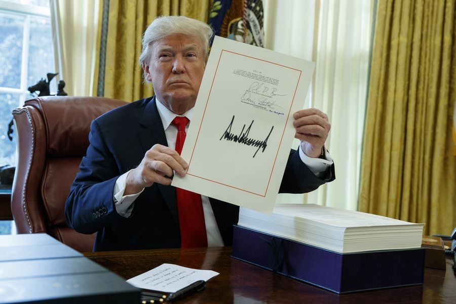 President Donald Trump shows off the tax bill after signing it in the Oval Office of the White House, Friday, Dec. 22, 2017, in Washington.