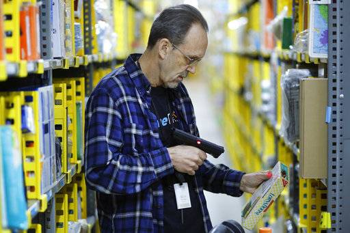 In this Wednesday, Dec. 20, 2017, photo, a clerk picks an item from a shelf and scans it with a hand-held device to fill a customer order at the Amazon Prime warehouse in New York.