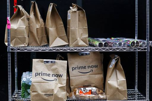 In this Wednesday, Dec. 20, 2017, photo, Amazon Prime Now bags are ready for delivery, at the Amazon warehouse in New York.