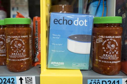 In this Wednesday, Dec. 20, 2017, photo, the Amazon Echo Dot is stocked on a shelf alongside jars of Garlic Chili Sauce at the Amazon Prime warehouse in New York.