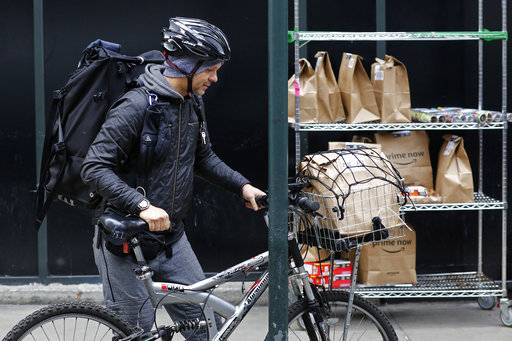 In this Wednesday, Dec. 20, 2017, photo, a bicyclist with a backpack and basket of customer orders prepares to make deliveries for Amazon Prime Now, in New York.