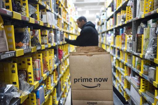 In this Wednesday, Dec. 20, 2017, photo, a clerk reaches to a shelf to pick an item for a customer order at the Amazon Prime warehouse, in New York.