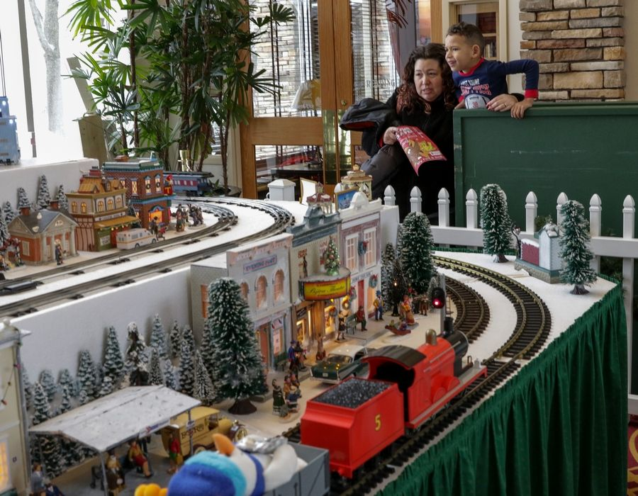 Sarah DuBose of Huntley and her son, Donovan, 5, view the holiday train display in the Prairie Lodge at Sun City in Huntley on Sunday.