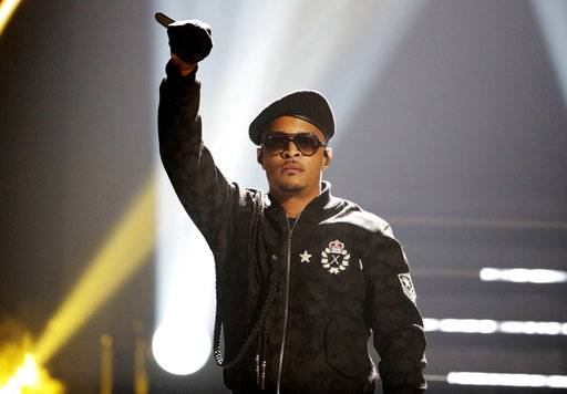 FILE - In this Sept. 17, 2016, file photo, T.I. performs during the BET Hip Hop Awards in Atlanta. Rapper T.I. spent Christmas eve spreading holiday cheer among some single mothers, helping them with their last-minute shopping for gifts. In a video T.I. posted on social media, the Grammy-winning artist entered an Atlanta-area Target on Sunday, Dec. 24, 2017, and called for all single mothers present to follow him. He strolled through the store alongside several mothers, went to the cash register with them and then paid for their Christmas presents.