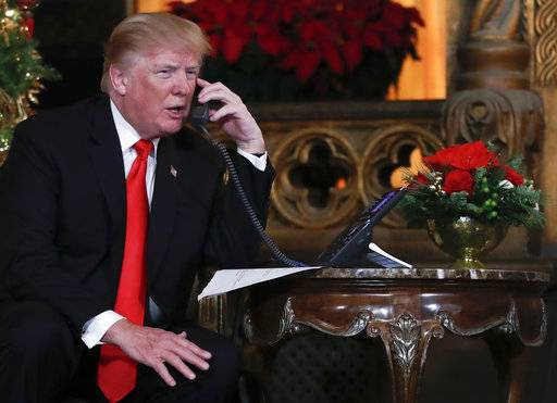President Donald Trump speaks on the phone Sunday with children as they track Santa Claus' movements with the North American Aerospace Defense Command (NORAD) Santa Tracker on Christmas Eve at the president's Mar-a-Lago estate in Palm Beach, Florida.