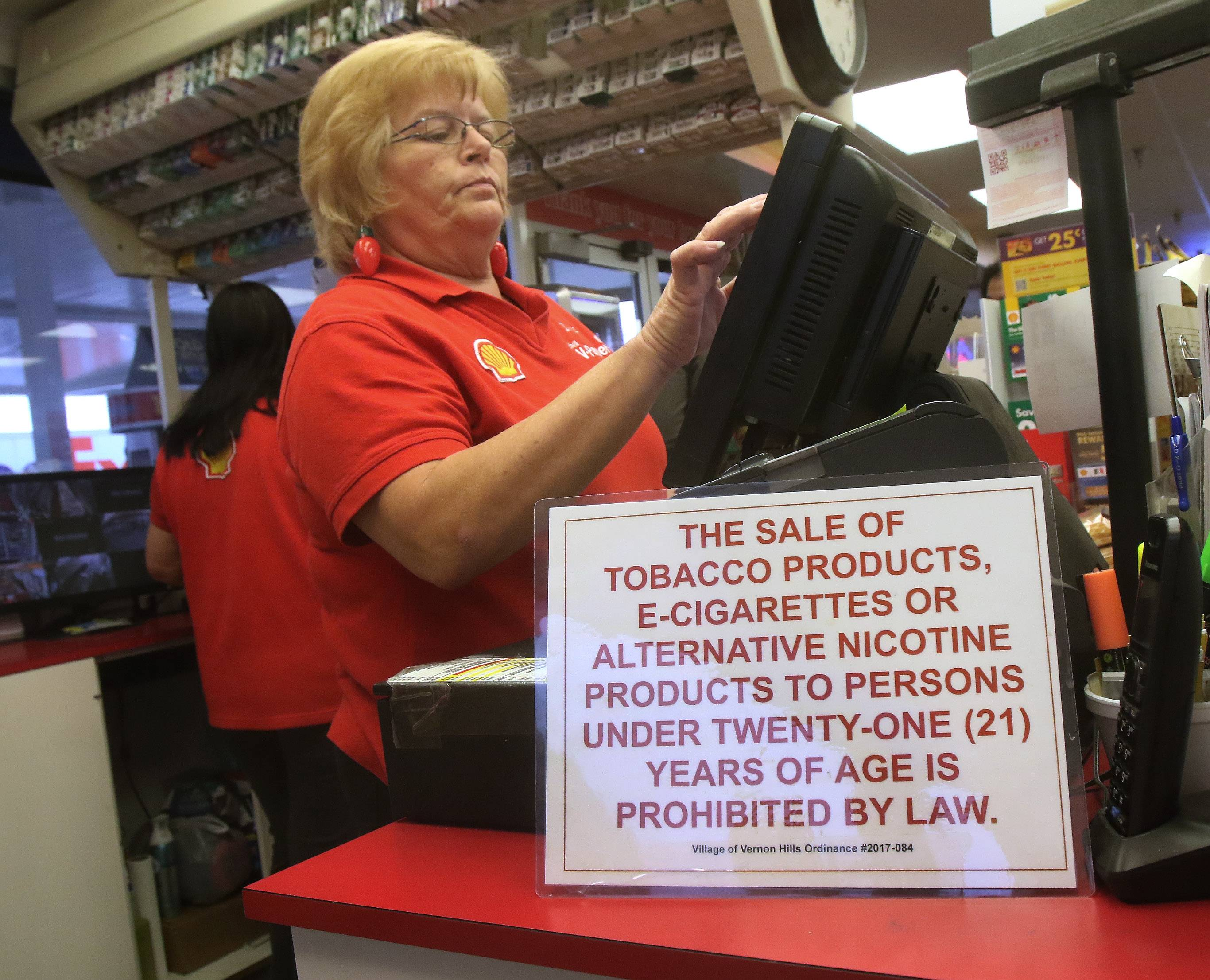 A sign stating the minimum age for purchasing cigarettes is 21 sits near sales associate Donna Mordica's cash register at Ernie's Shell station in Vernon Hills. The village is one of six towns in Lake County to increase the minimum age for buying tobacco products to 21, from 18.