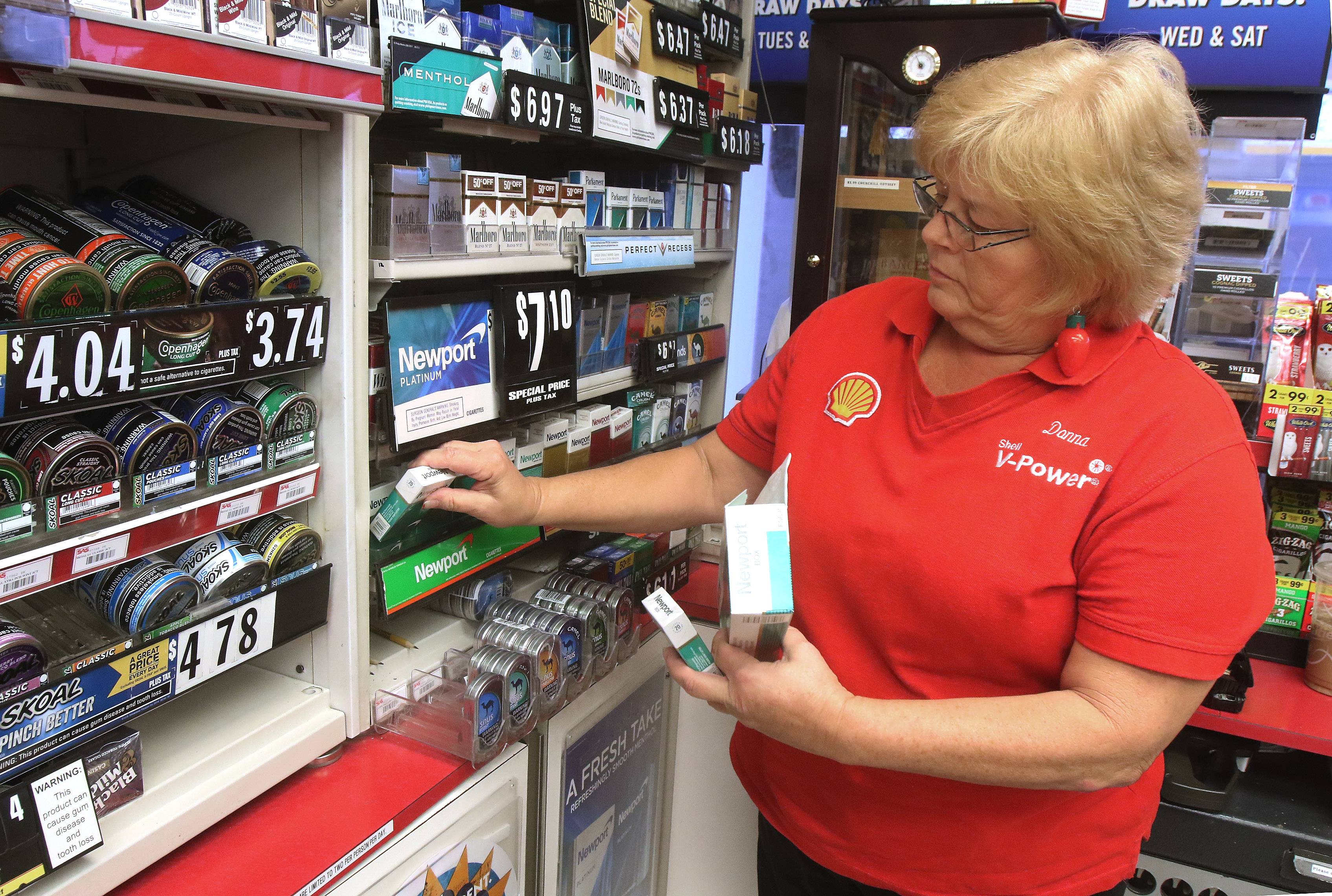 Sales associate Donna Mordica stocks the cigarette shelves at Ernie's Shell station in Vernon Hills. Chicago and a dozen suburbs have increased the minimum age for buying cigarettes and other tobacco products to 21.