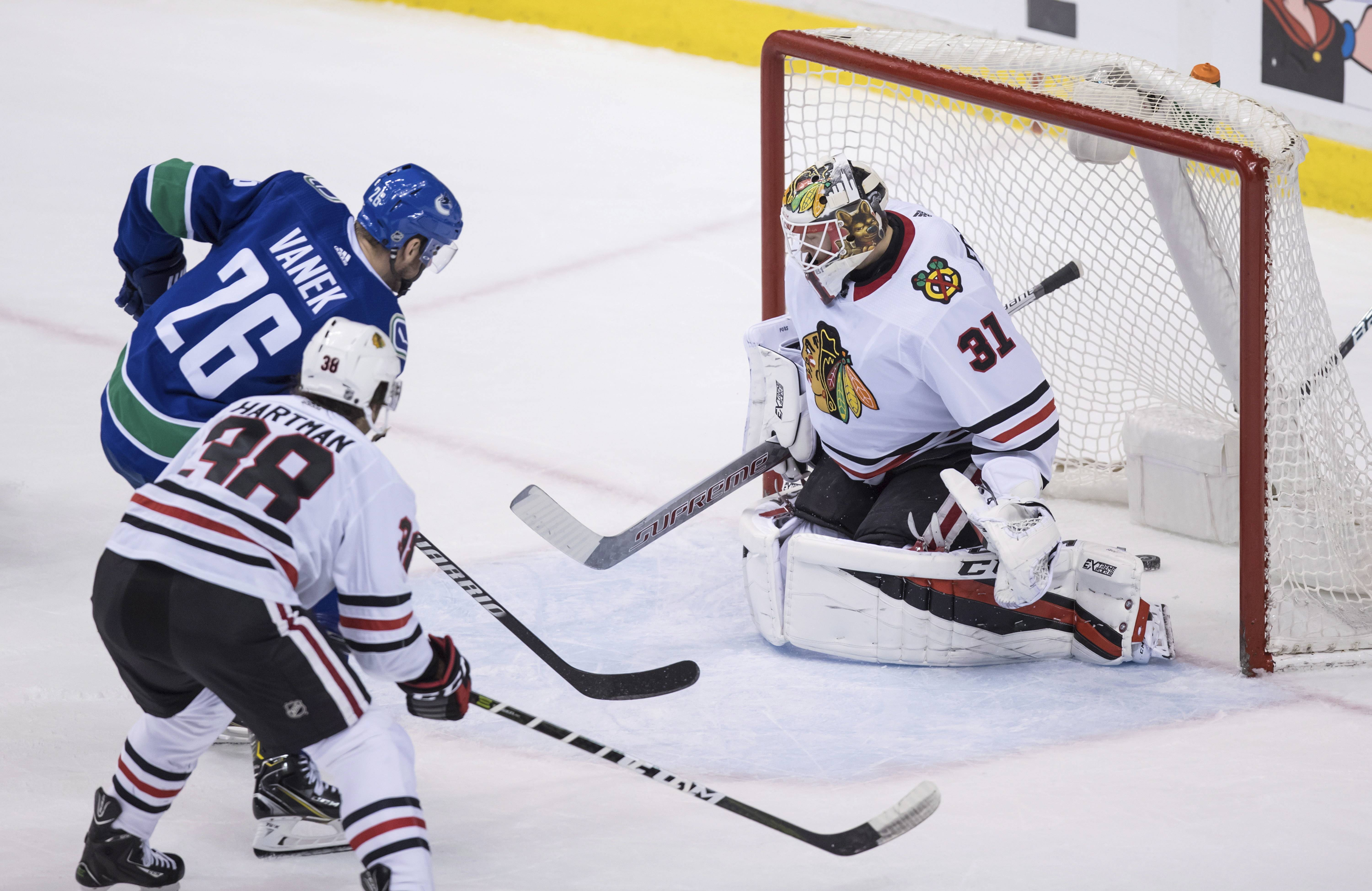 Vancouver Canucks' Thomas Vanek (26), of Austria, scores against Chicago Blackhawks goalie Anton Forsberg, right, of Sweden, as Ryan Hartman watches during the second period of an NHL hockey game Thursday, Dec. 28, 2017, in Vancouver, British Columbia. (Darryl Dyck/The Canadian Press via AP)