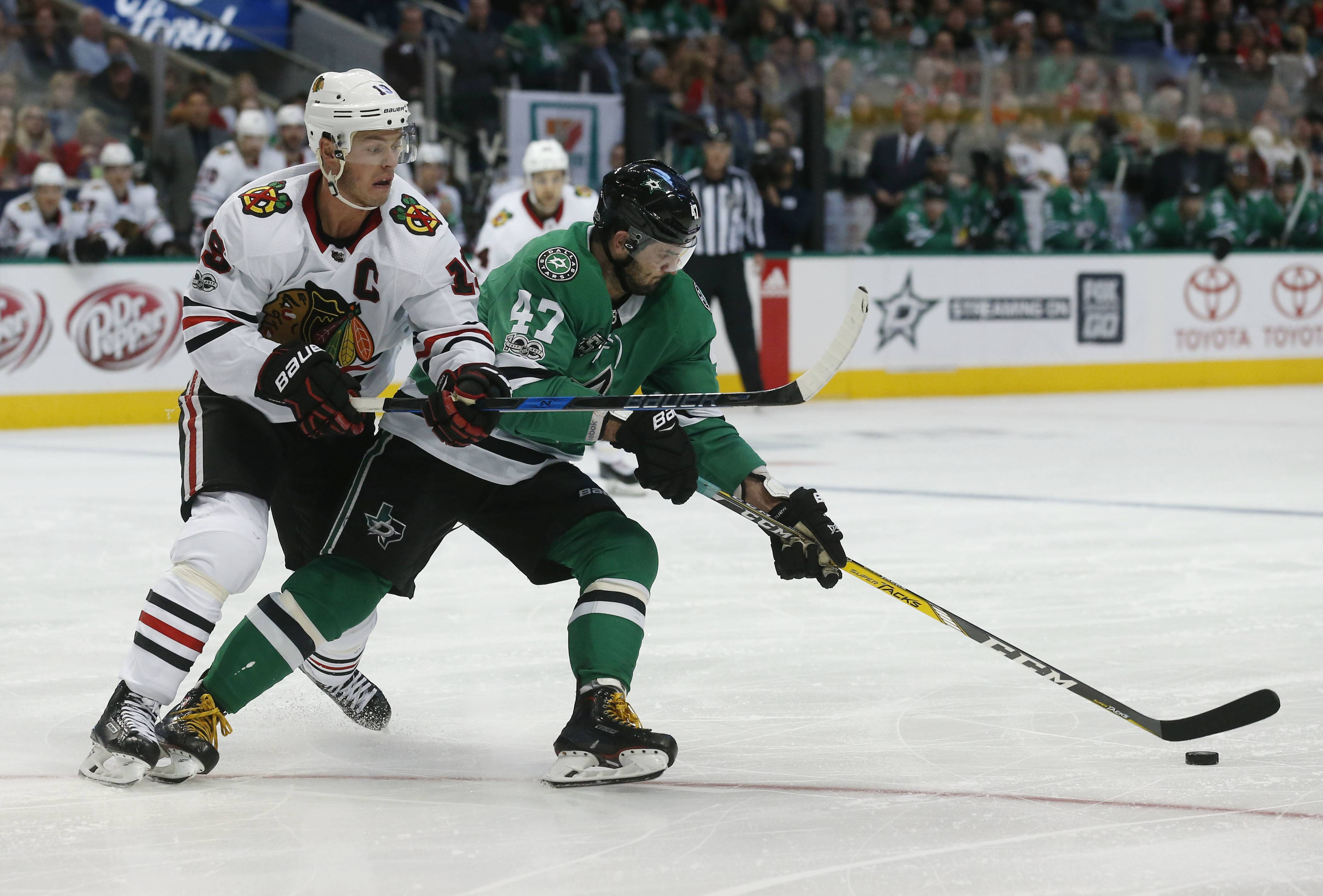 Chicago Blackhawks center Jonathan Toews (19) and Dallas Stars right wing Alexander Radulov (47) battle for the puck during the second period of an NHL hockey game, Saturday, Dec. 2, 2017, in Dallas.