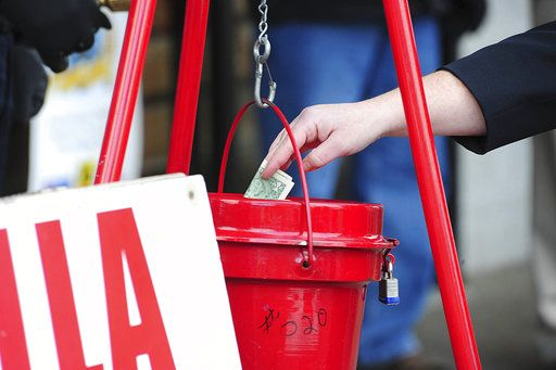 FILE - In this Nov. 22, 2017, file photo, a patron donates money in a Salvation Army red kettle in Wilkes-Barre, Pa. In this season of giving, charity seems to be getting an extra jolt because the popular tax deduction for charitable donations will lose a lot of its punch.  (Mark Moran/The Citizens' Voice via AP)