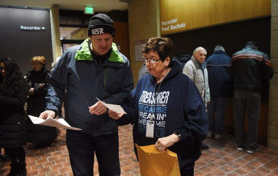Paul Nockels, who lives in Downers Grove, avoids the line by handing a check for his prepaid tax bill to DuPage County Treasurer Gwen Henry.