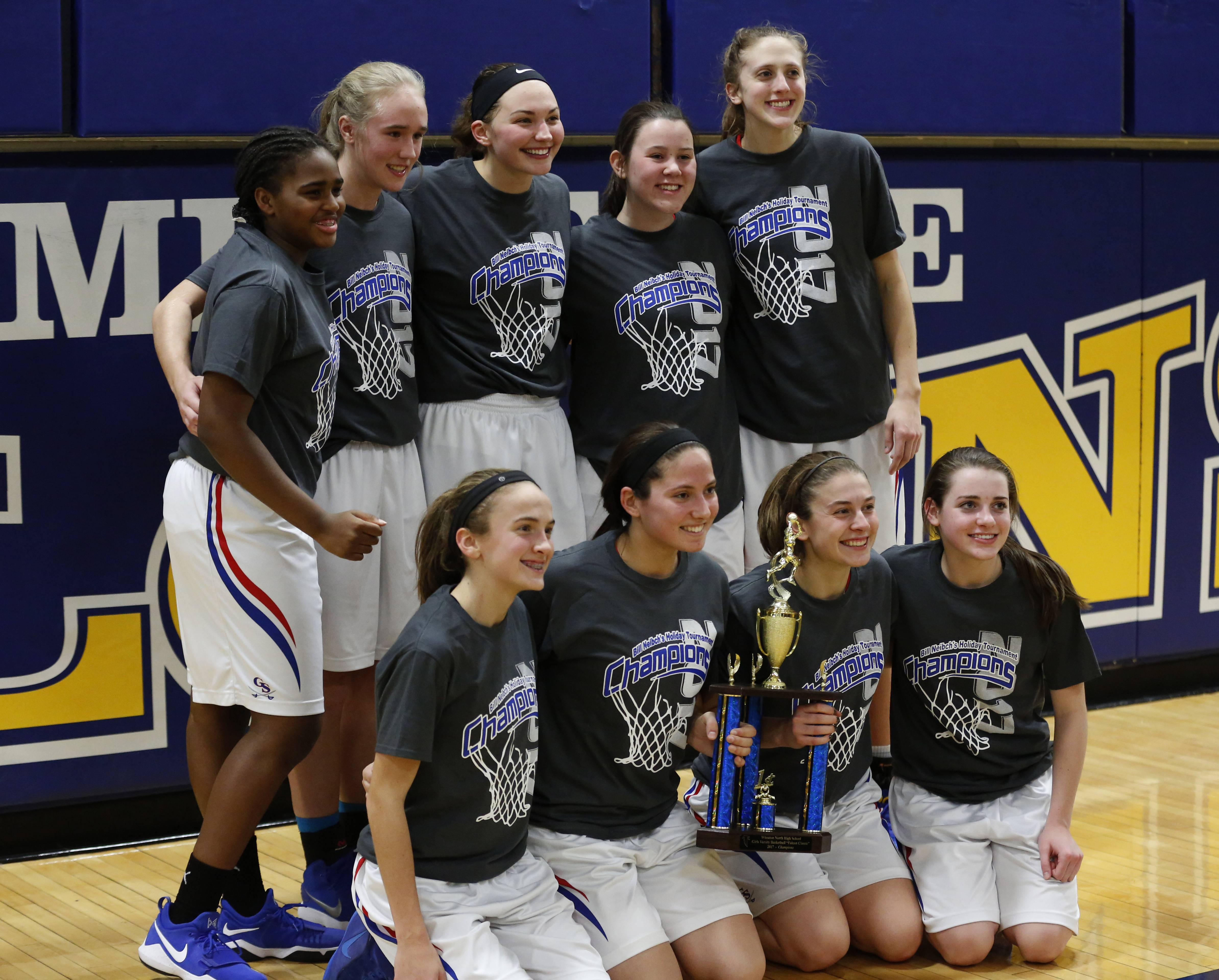 Glenbard South players celebrate their 40-27 win over West Aurora to capture the Wheaton North Bill Neibch Falcon girls basketball holiday tournament championship.