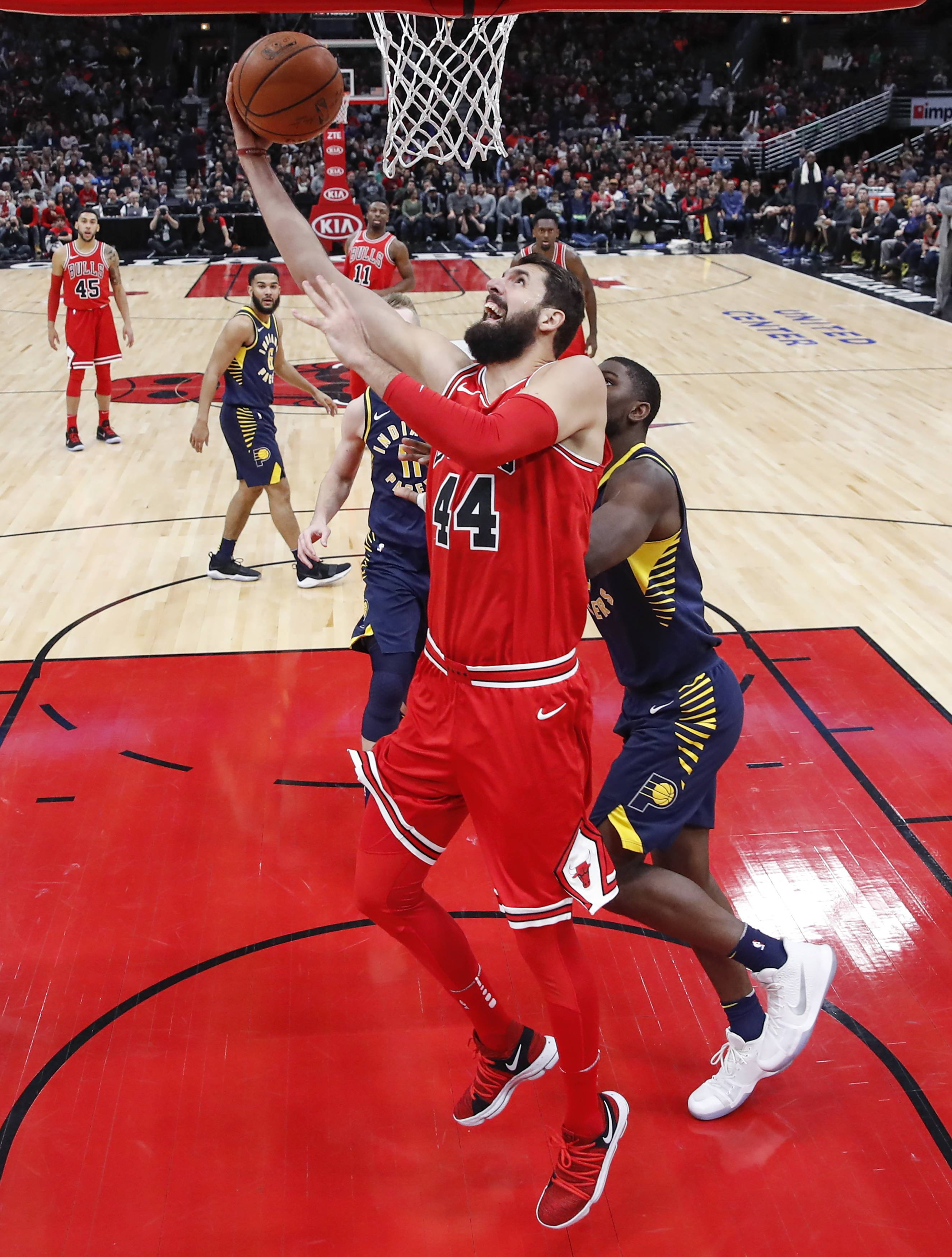 Chicago Bulls forward Nikola Mirotic, center, goes to the basket against Indiana Pacers forward Alex Poythress, right, during the first half of an NBA basketball game, Friday, Dec. 29, 2017, in Chicago.