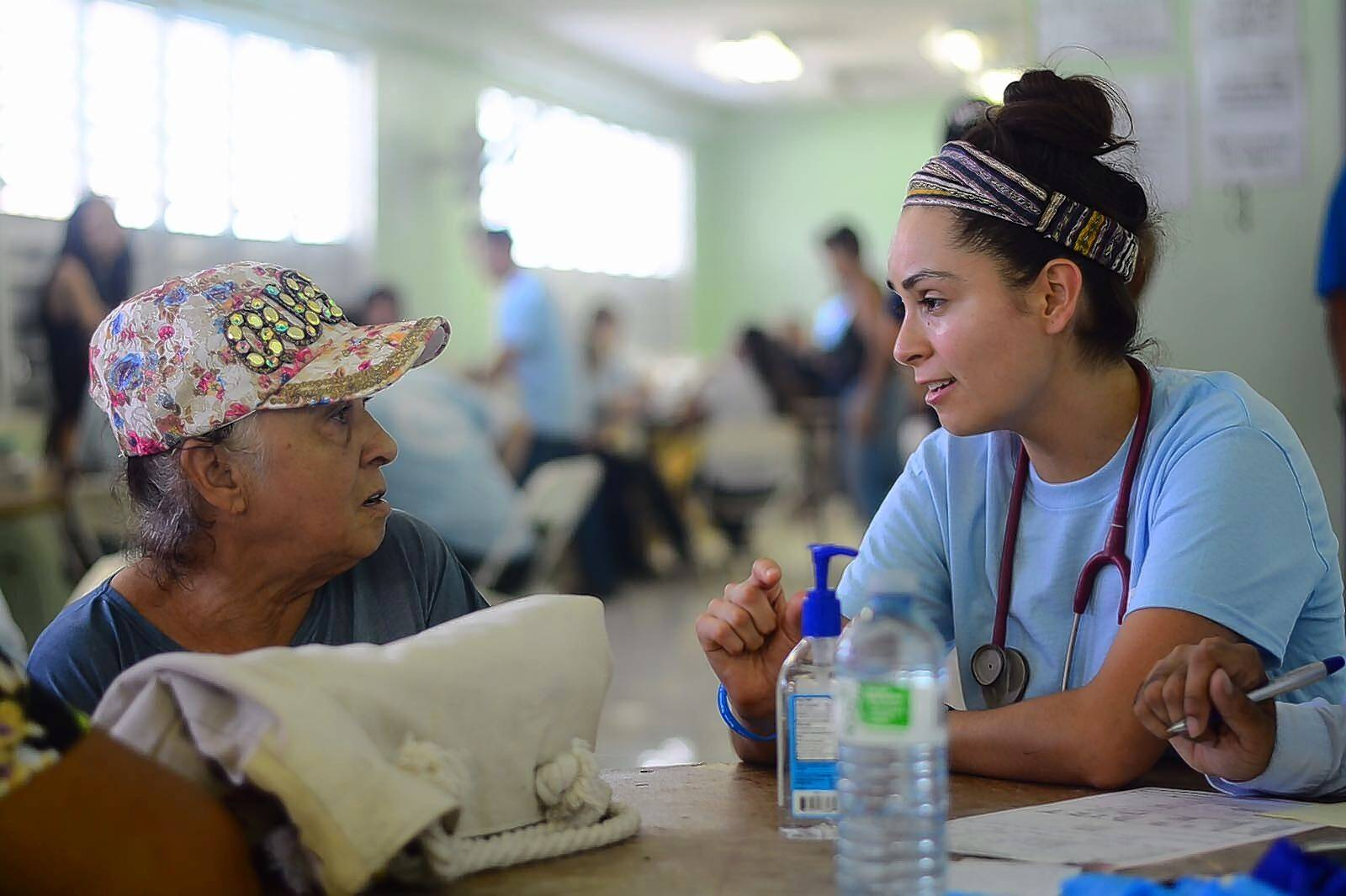 Maria Soriano, right, a cardiovascular nurse at Elmhurst Hospital, meets with a patient in Puerto Rico during a medical relief mission in October 2017 following hurricanes that devastated islands throughout the Caribbean.
