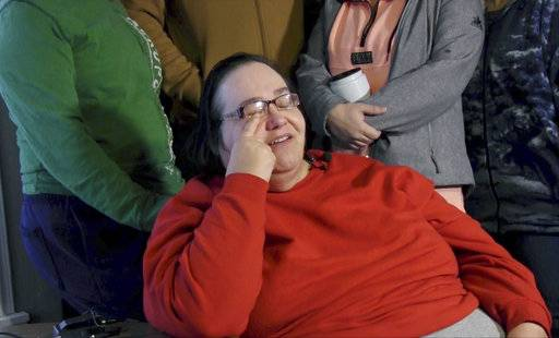 "Lisa Finch, surrounded by family members reacts to the killing of her son Andrew Finch after he was shot Thursday evening, Dec. 28, 2017, by police, in Wichita, Kan. Authorities are investigating whether the deadly police shooting stemmed from someone making up a false report to get a SWAT team to descend upon a home in a prank common in the online gaming industry known as ""swatting."" (Bo Rader /The Wichita Eagle via AP)"