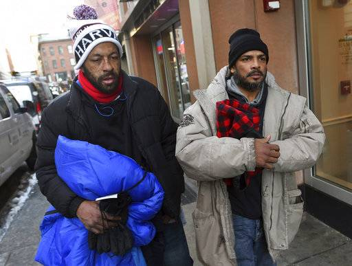 "In this Wednesday, Dec. 27, 2017, photo, homeless men Sean Stuart, left, and Segundo Rivera walk on a street after spending the day at St. Francis House in Boston. With temperatures across Massachusetts not expected to rise above freezing for days, politicians and advocates for the homeless are particularly concerned about getting as many people as possible into shelters. Stuart and Rivera told the Boston Herald that they're not comfortable spending the night in a shelter. ""We've lived out here so long it's like honestly, this is comfortable for us,"" Rivera said. (Christopher Evans/The Boston Herald via AP)"