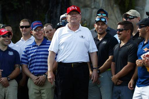 President Donald Trump smiles as he meets with members of the U.S. Coast Guard, who he invited to play golf, at Trump International Golf Club, Friday, Dec. 29, 2017, in West Palm Beach, Fla. (AP Photo/Evan Vucci)