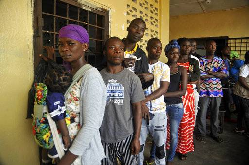 People wait to cast their votes during a Presidential runoff election in Monrovia, Liberia, Tuesday Dec. 26, 2017, Young Liberians went straight from all-night Christmas celebrations to the polls Tuesday for a runoff election between a former international soccer star and the vice president to replace Africa's first female head of state. (AP Photo/Abbas Dulleh)